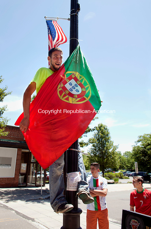 Naugatuck, CT-16 June 2014-061614BF01-  Portugal soccer fan Vitor Guedes, 27, from Naugatuck who is originally from Porto, Portugal, hangs a flag on a light post outside Santos Restaurant on Church Street in Naugatuck Monday afternoon. It was a standing room only crowd who showed up to support the team who were defeated by Germany 4-0 in Group G play at Arena Fonte Nova, in Salvador, Brazil.  Bob Falcetti Republican-American