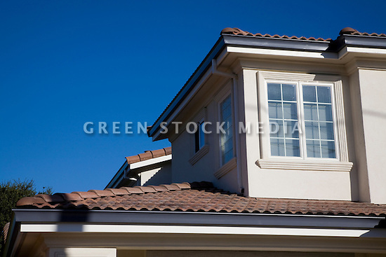 A close up of a large two-story conventional wood frame house with red brick roof that was recently finished. Cupertino, California, USA