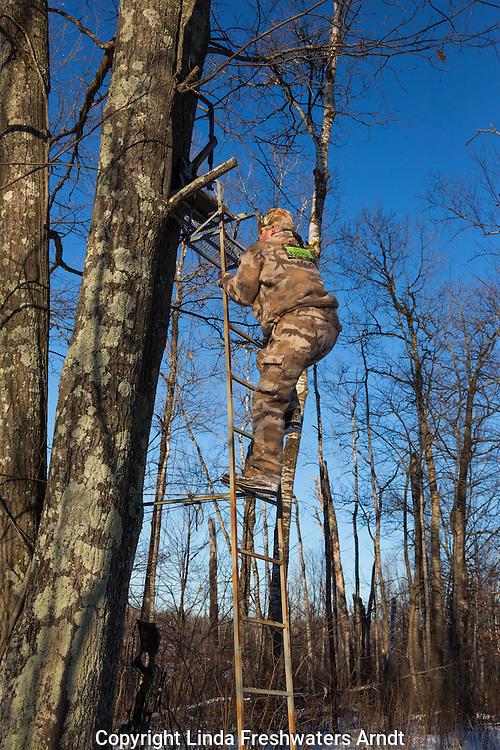 Crossbow hunter climbing up a ladder stand