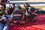Firefighters transporting patients from a rush red tarp at a mass casualty incident