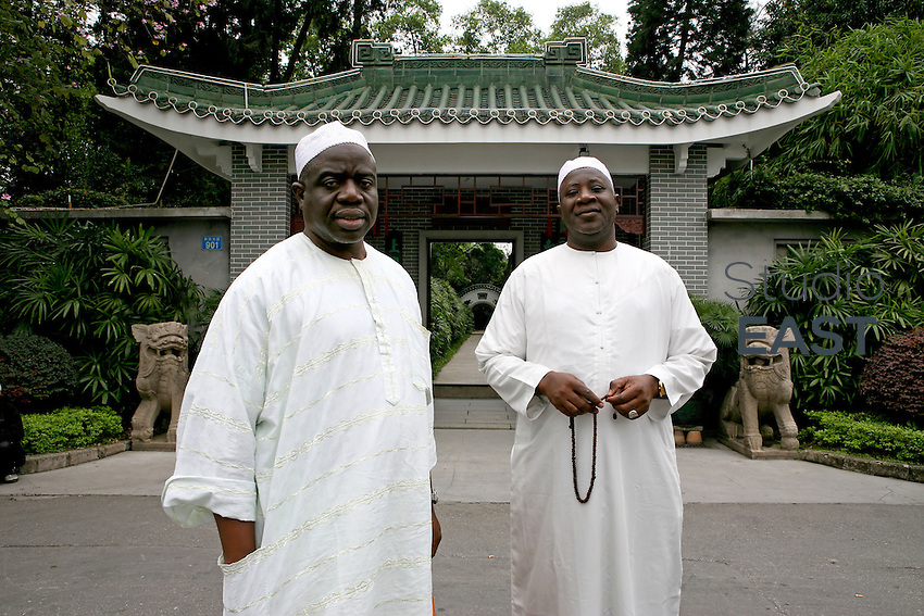 Two muslims wear a traditional outfit in front of Guangzhou mosque's entrance, in Guangzhou, China, on March 16, 2007. Chinese goods flow to Africa, but men flow the other way: thousands of Africans are now settling in China. China's Southern metropolis Guangzhou has the country's largest African population, now exceeding 7,000. Photo by Patrick Wack/Pictobank