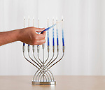 Man's hand lighting menorah
