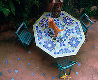 The geometric motifs from an octagonal mosaic table are picked out in the terracotta floor tiles of this secluded courtyard garden