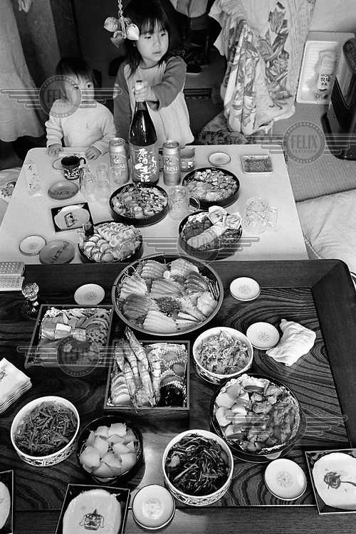 A variety of traditional dishes prepared for New Year dinner. The father of the two girls has brought sake to accompany the feast.