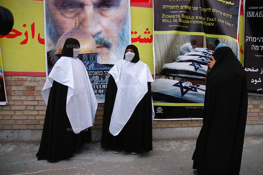 """2004..Women kamikaze candidates entirely veiled take pictures in front of propaganda posters during the meeting of """"Commemorating Martyrs of the Global Islamic Movement"""" in the Behesht-e-Zahra cemetery...Des candidates kamikazes complètement voilées se prennent en photo devant des affiches de propagande lors du meeting du groupe """"Commemorating Martyrs of the Global Islamic Movement"""" dans le cimetière Behesht-e-Zahra."""