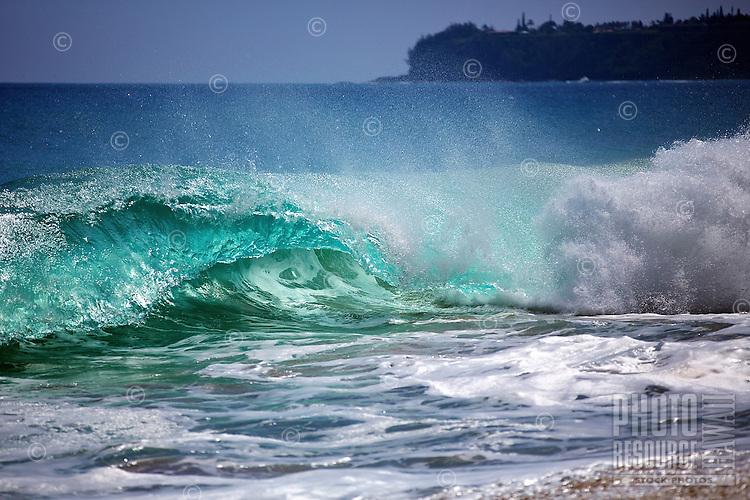 A beautiful, glassy turquoise wave crashes into spray and white foam at Lumaha'i Beach on the north shore of Kaua'i.