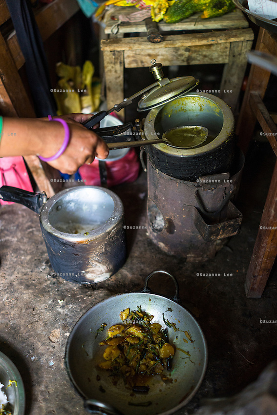 Kalpana Tamang (40), uses the kitchen utensils that was given to her in the 'Home-in-a-Box' as she cooks lunch in her temporary shelter in Kavre, Bagmati, Nepal on 30 June 2015.  Kalpana, a widow with 3 children, has been supported by SOS Children's Villages for many years now and had receive the Home-in-a-Box after the earthquake destroyed her house, almost killing her two daughters. She now lives in a temporary shelter, sharing her dwelling with farm animals, and is trying to make ends meet by weaving bamboo baskets to supplement the financial assistance provided by SOS Childrens Villages. The NGO mostly supports her children's welfare and schooling as well as provides her with essential household and schooling items like kitchen utensils and school books and uniforms. Photo by Suzanne Lee for SOS Children's Villages
