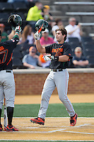 Garrett Kennedy (40) of the Miami Hurricanes knocks helmets with teammate Christopher Barr (17) after hitting a home run against the Wake Forest Demon Deacons at Wake Forest Baseball Park on March 21, 2015 in Winston-Salem, North Carolina.  The Hurricanes defeated the Demon Deacons 12-7.  (Brian Westerholt/Four Seam Images)