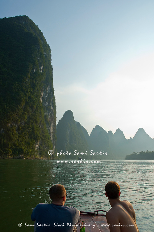 Tourists looking across the Li Jiang River at the limestone mountain peaks between Xinping and Yangshuo, Guangxi, China.