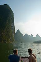 Tourists looking across the Li Jiang River at the limestone mountain peaks between Xinping and Yangshuo, Guangxi, China.