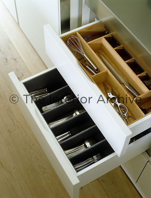 A pair of open drawers containing cutlery and a range of kitchen utensils
