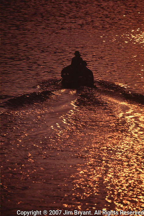 Silhouetted by the setting sun, a fisherman heads home to Praia Bay in Terceira, Azores. Far out in the Atlantic Ocean, some 850 miles off the western coast of Lisbon, Portugal lies the 425-mile long archipelago of the Azores. (Jim Bryant Photo).....
