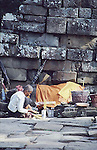 ELDERLY MAN BURNS INCENSE AT ANGKOR WAT