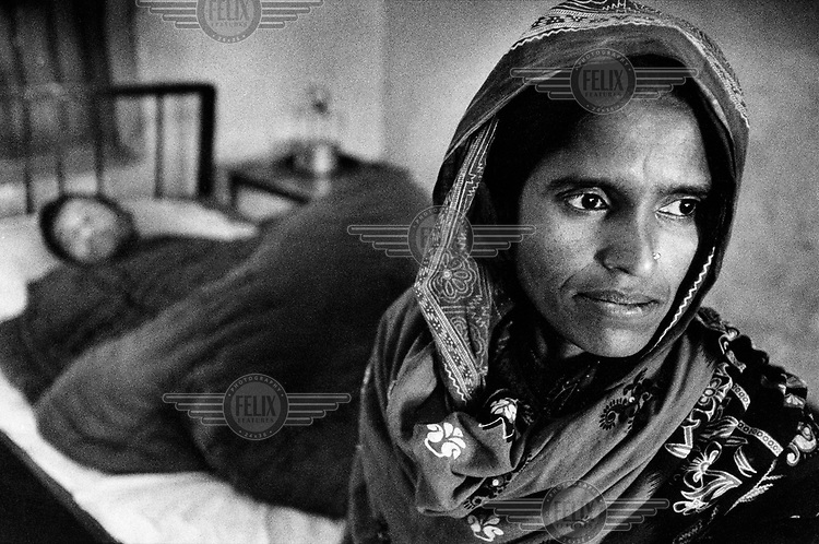 A woman at the bedside of her husband, who is suffering from tuberculosis (TB).