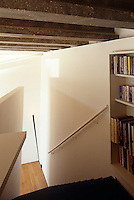 Bookshelves have been incorporated into the wall on the landing at the top of the stairs