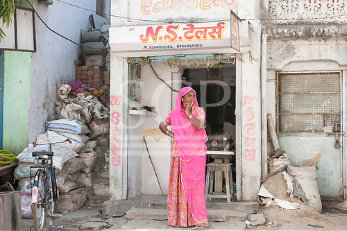 Rajasthan, India. Between Jodhpur and Jaipur. Woman standing outside her tiny sewing shop with her sewing machine in traditional Rajasthan pink sareelooking along the street with her fingers over her mouth.