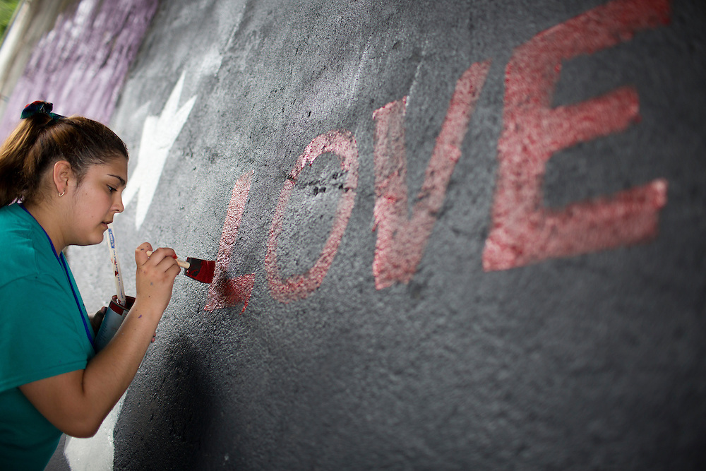 "Erica Meneses works on a mural beneath a train bridge during ""Circle the City with Service,"" the Kiwanis Circle K International's 2015 Large Scale Service Project, on Wednesday, June 24, 2015, in Indianapolis. (Photo by James Brosher)"