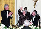 Former first lady Lady Bird Johnson, center, waves as United States President Bill Clinton applauds, left, and former U.S. President George H.W. Bush, right, helps steady her at the 200th Anniversary of the White House Dinner in the East Room of the White House in Washington, D.C. on November 9, 2000. <br /> Credit: Ron Sachs / CNP