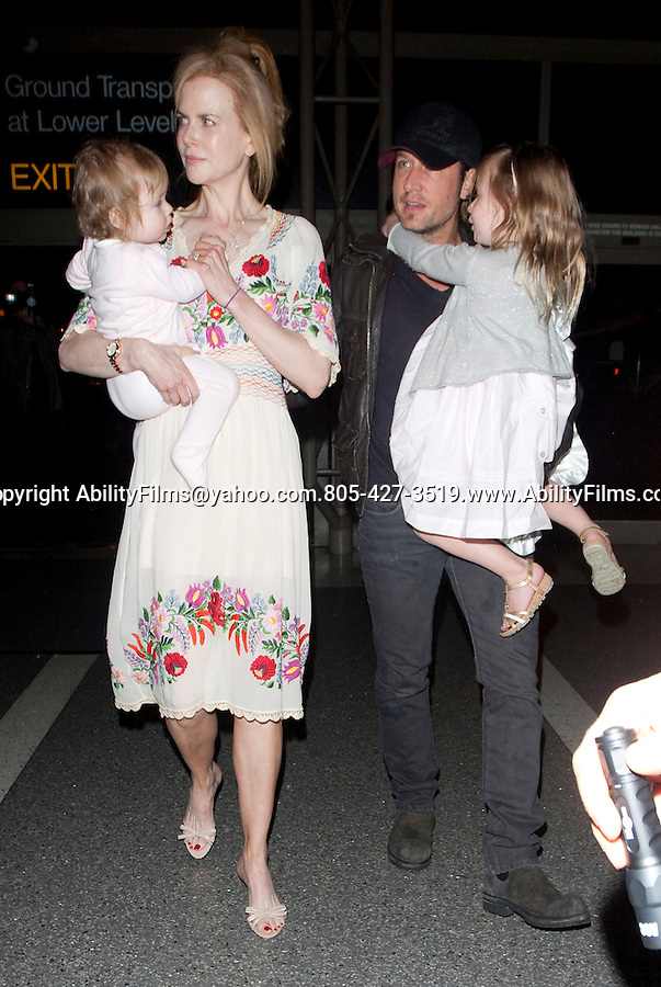 .March 14th 2012 ..Nicole Kidman & Keith Urban carrying their sleepy kids through the LAX airport in Los Angeles California. Nicole was wearing a white red flower dress ..AbilityFilms@yahoo.com.805-427-3519.www.AbilityFilms.com..