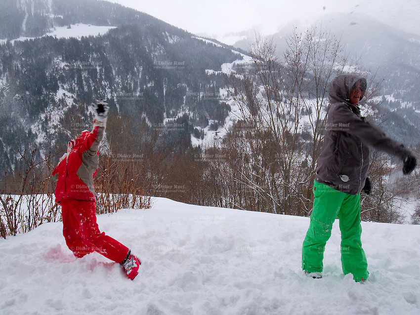 Switzerland. Canton Valais. Sarreyer is a village located in the Bagnes valley. Snow in the winter. Nicola Ruef (L) and Micaela Ruef (R) have a snowball fight outside of the chalet. 6.01.2012 © 2012 Didier Ruef