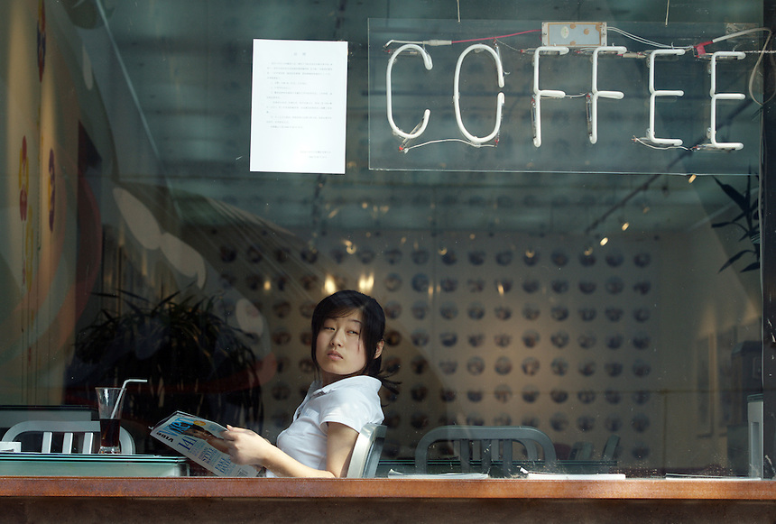 A woman reads a magazine in a coffee shop that is part of Time Zone 8 bookshop in Dashanzi. China's art scene is becoming popular among foreign art collectors pushing prices higher.