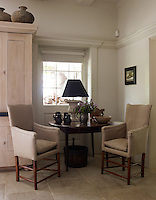 A corner of the stone-flagged kitchen is furnished with a pair of line-covered armchairs and an antique table