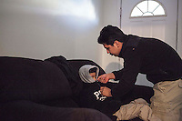Ivan Maldonado (black jacket) works night shifts at a local factory to help support his mother and younger brothers. Ivan left school to work after his father was deported. Everyday he wakes early to prepare his youngest brother Kevin for school because thier mother works a 12 hour shift beginning at 5 AM. Brendan Bannon. Painesville, Ohio, March 26, 2014.