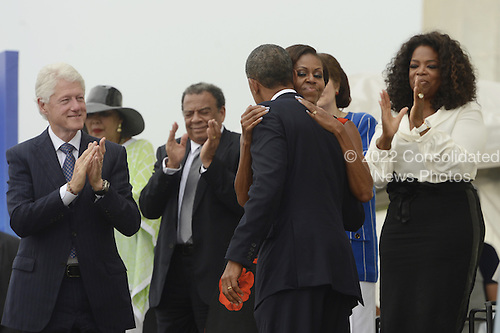 US President Barack Obama (C) hugs First Lady Michelle Obama (2-R) as former US President Bill Clinton (L) and Oprah Winfrey (R) look on, during the 'Let Freedom Ring' commemoration event, at the Lincoln Memorial in Washington DC, USA, 28 August 2013. The event was held to commemorate the 50th anniversary of the 28 August 1963 March on Washington led by the late Dr. Martin Luther King Jr., where he famously gave his 'I Have a Dream' speech.<br /> Credit: Michael Reynolds / Pool via CNP