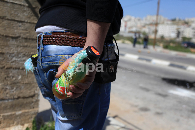 A Palestinian protester carries molotov cocktails during clashes with Israeli soldiers at a protest calling for the release of Palestinian prisoners held in Israeli jails, outside Israel's Ofer military prison near the West Bank city of Ramallah April 4, 2014. Israel has called off a planned release of Palestinian prisoners meant to advance the U.S.-sponsored peace process and called for a review of how the troubled negotiations can make progress, an official briefed on the talks said on Thursday. Photo by Issam Rimawi