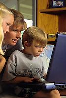 Mother and sister watch as a young boy works at a laptop computer.