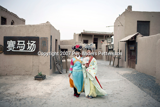 """DUNHUANG, CHINA - JUNE 7: Chinese women dress up in clothes from the movie """"Dunhuang, filmed in 1987, on June 7, 2007 in a village outside DunHuang, China. A complete movie town was built and left here. It is now a tourist attraction. About 20 other movies and television series has been shoot here since then, and it's an especially popular attraction fro Japanese tourists as the movie was made in cooperation with Japan. DonHuang was a strategic important stop on the ancient Silk Road and many tourists come here to ride on camels, sand surfing and trek in the desert. (Photo by Per-Anders Pettersson)..."""
