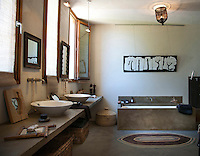 """This bathroom has a concrete floor matched with a bath and washstand clad in a waxed concrete and the artwork above the bath is titled """"Festival"""" and signed Princesse M"""