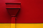 Side of building with large drain painted red and yellow