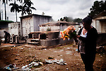 A Guatemalan prepares to lay flowers at a gravesite to celebrate Dia de los Muertos at Cementario General, in Guatemala City, Guatemala, on Tuesday, Nov. 1, 2011.