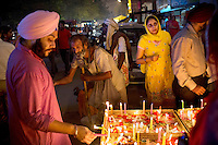 Men light candles in front of a temple on the occasion of Diwali, one of the biggest festival for Hindus.