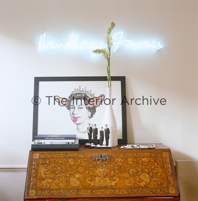 A 1970s British humourus print resting on a French writing bureau with a neon lighting installation hanging above it