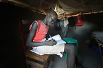 Yar Yorlu, 14, does his homework in his family's shelter in the Rhino Refugee Camp in northern Uganda. As of April 2017, the camp held almost 87,000 refugees from South Sudan, and more people were arriving daily. About 1.8 million people have fled South Sudan since civil war broke out there at the end of 2013. About 900,000 have sought refuge in Uganda.