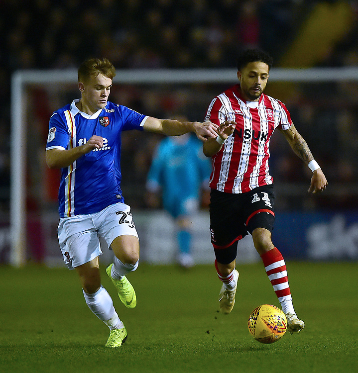Lincoln City's Bruno Andrade vies for possession with  Exeter City's Archie Collins<br /> <br /> Photographer Andrew Vaughan/CameraSport<br /> <br /> The EFL Sky Bet League Two - Lincoln City v Exeter City - Tuesday 26th February 2019 - Sincil Bank - Lincoln<br /> <br /> World Copyright © 2019 CameraSport. All rights reserved. 43 Linden Ave. Countesthorpe. Leicester. England. LE8 5PG - Tel: +44 (0) 116 277 4147 - admin@camerasport.com - www.camerasport.com