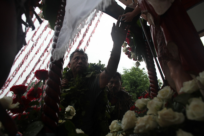 "A man touches a statue of St. John the Baptist during the annual Taong Putik, or ""mud people,"" festival in Bibiclat, on Luzon island, Philippines. During the festival, devotees cover themselves in mud, banana leaves and other vines, which symbolize the animal skins that St. John the Baptist wore in the Bible. June 24, 2011."