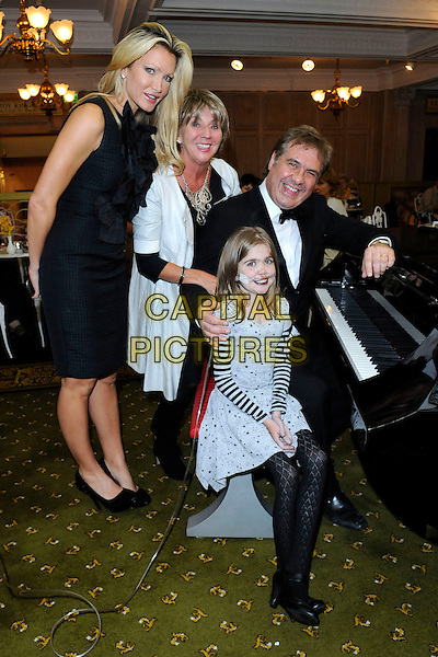CAPRICE BOURRET, SUE JOHNSON & KIRSTY HOWARD .Lunch at Harrods to celebrate Kirsty's 14th birthday, Knightsbridge, London, England. .September 18th, 2009.full length black dress sleeveless blue dress sitting on lap piano.CAP/FIN.©Steve Finn/Capital Pictures.