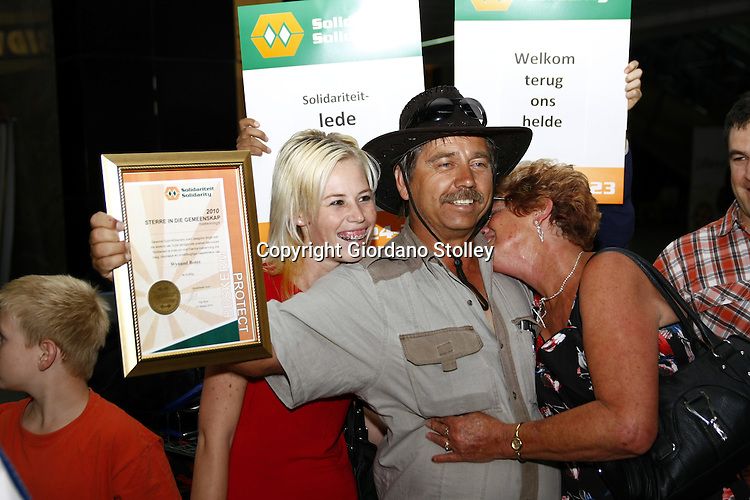 JOHANNESBURG - 23 October 2010 - Wynand Botes, one of four South Africans involved in the Chile Mine rescue,  holds up his Stars in the Community award given to him by the Solidarity trade union shortly after his arrival at OR Tambo International Airport where daughter Thelma (Left) and his wife Marie (Right) welcomed him home -- APP/Allied Picture Press