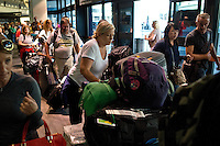 United Airlines passenger Katherine Wells pushes two luggage trolleys in a long line to rebook her family's flight home to Sydney, Australia. Flight delays were caused by the Asiana Airlines Flight 214 crash on the runway of San Francisco International Airport in SAN FRANCISCO, CALIFORNIA, on 6 July 2013. (Alvin Jornada/European Pressphoto Agency)