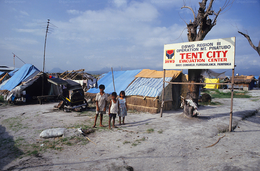 VOLCANO AFTERMATH, Philippines. Tent city refugee camp.Central Luzon, Mount Pinatubo volcano erupted in 1991  and caused massive destruction of urban and rural landscape. Many indigenous  Aeta and Igorot people were displaced. White volcanic  ashes settled and disfigured the landscape.   Many  live in ramshackle shelters, in  refugee camps and settlements, living on humanitarian aid.