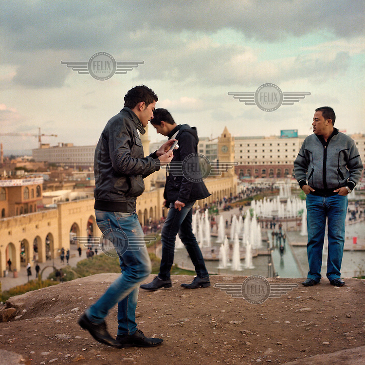 Three men stand on the edge of the Cidadel of Arbil above Hewler (Hawler) Park in the Iraqi city of Erbil. The Citadel is an inhabited mound in the centre of the modern Iraqi city of Erbil, which is said to be one of the oldest, continually inhabited places in the world. Earliest traces of habitation on the mound date back to the 5th millennium BC, possibly earlier. The city of Erbil, the fourth biggest in Iraq, is today the capital of Iraqi Kurdistan. .Since 2007 the High Commission for Erbil Citadel Revitalisation (HCECR) has been in charge of the Citadel complex and is carrying out major reconstruction efforts since moving out all remaining residents. It is hoped that 50 families will move back into the Citadel once renovation work and archeological digs have been completed. .