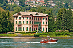 A boat passes in front of a pink villa on the shores of the Lake Como town Cernobbio, Italy