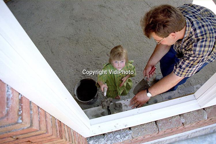 Foto: VidiPhoto..DODEWAARD - De kleine Gertine van Laar uit Dodewaard helpt haar vader bij het bouwen van een woning van 500 kuub. Papa Jacob heeft van de .gemeente Dodewaard toestemming gekregen om een woning in het agrarische buitengebied te bouwen: en dat is nog steeds een uitzondering. En aangezien Jacob van Laar bouwvakker is, bouwt hij zijn huis zelf. De driejarige Gertine wil het vak ook leren, dus helpt ze een handje.