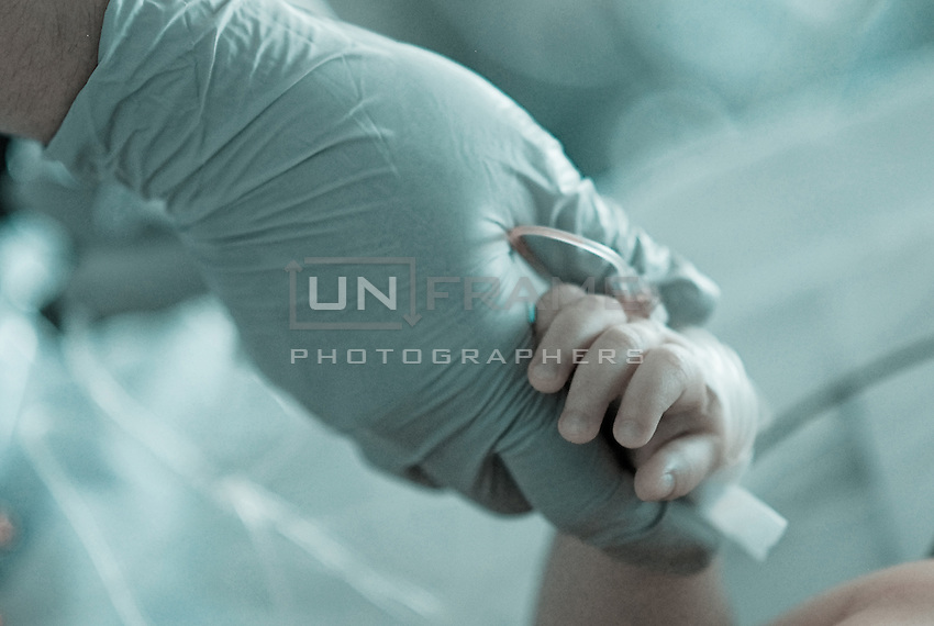 Hand of the ICU nurse holds the hand of child