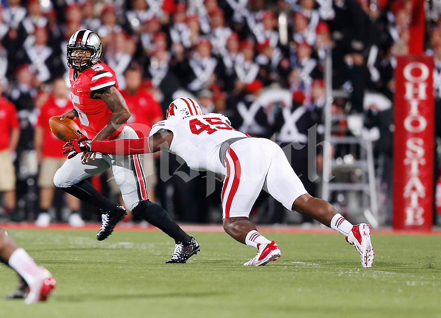 Ohio State Buckeyes quarterback Braxton Miller (5) eludes Wisconsin Badgers nose tackle Warren Herring (45) as he looks downfield for an open receiver in first half action at Ohio Stadium on September 28, 2013.  (Chris Russell/Dispatch Photo)