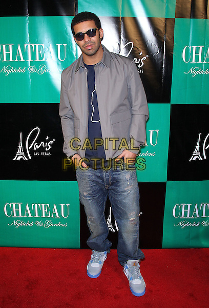 DRAKE (Aubrey Drake Graham).Grand Opening of Chateau Nightclub inside the Paris Resort Hotel and Casino,  Las Vegas, Nevada, USA, .5th March 2011..full length jacket sunglasses jeans blue t-shirt trainers hands in pockets grey gray .CAP/ADM/MJT.© MJT/AdMedia/Capital Pictures.