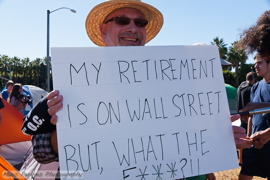 """Stan holds a sign saying """"My retirement is on Wall Street, but What the F***?"""" at the Occupy Orange County, Irvine camp on November 5."""